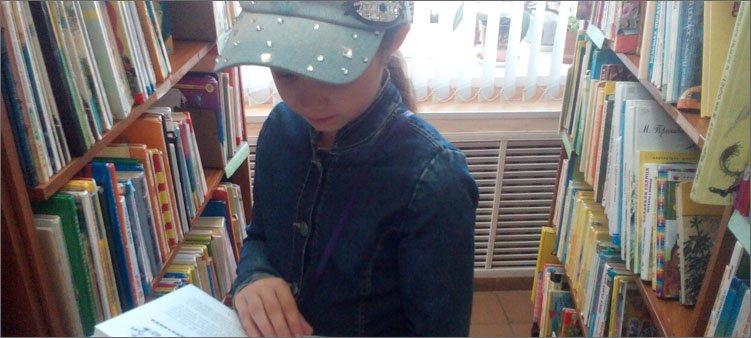 девочка-выбирает-книгу-в-библиотеке