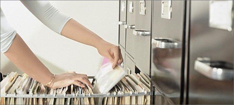 девушка-ищет-документы-в-шкафу