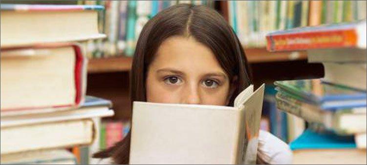 девочка-отличница-читает-книгу-в-библиотеке