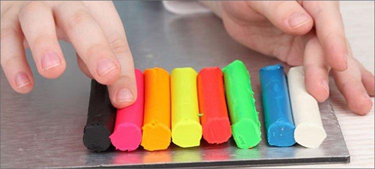 ребенок-трогает-цветной-пластилин-пальцем