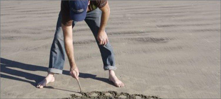 мужчина-рисует-палкой-на-песке