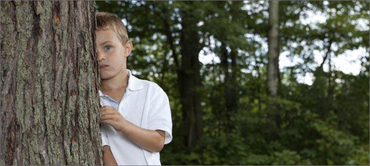застенчивый-мальчик-прячется-за-деревом