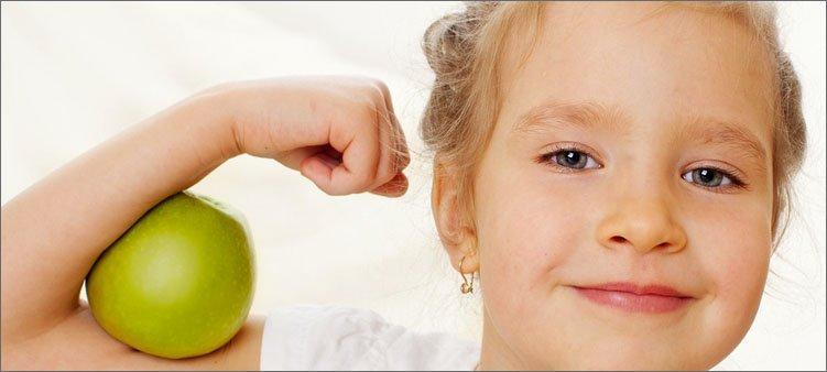 девочка-показывает-свою-силу-с-яблоком